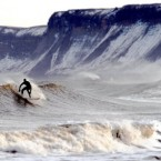 A surfer in high seas with snow covered cliffs in the background in Scarborough.
