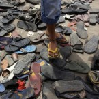 A young Bahraini anti-government protester slips into a pair of plastic shoes from a collection at Pearl roundabout in Manama, Bahrain, lost by people during Sunday's fierce clashes. (AP Photo/Hasan Jamali)
