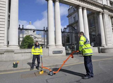 Gardai seal manhole covers outside Government Buildings this morning ahead of the visit of Queen Elizabeth next week.