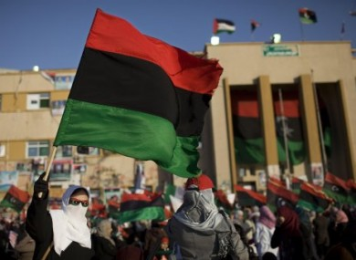 A Libyan woman holds a pre-Gaddafi flag during an anti-Gaddafi protest in Benghazi in April 2011.