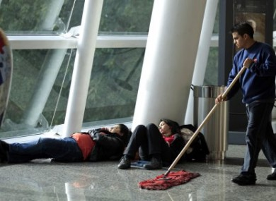 Two women rest as a man wipes the floor at Jorge newbery Airport in Buenos Aires, Argentina.