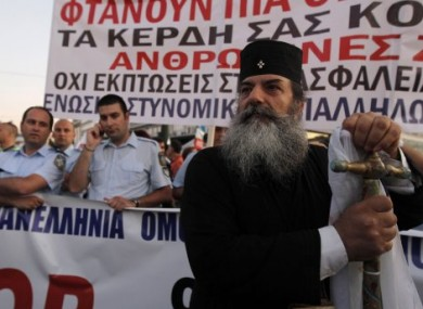 A priest stands in front of demonstrating police officers outside the Greek Parliament in Athens yesterday.