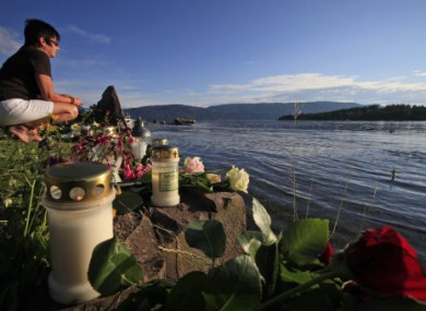 A woman sits among floral tributes to the victims of the shooting as she looks at Utoya island.