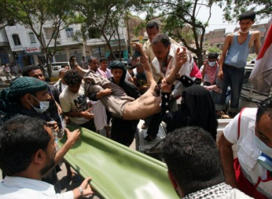 Anti-government protestors carry a wounded protestor from the site of clashes with security forces, in Taiz, Yemen, yesterday