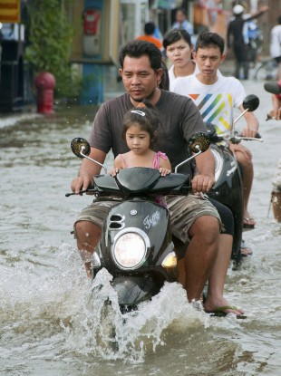 People ride motor scooters on a flooded street in a residential area of northern Bangkok