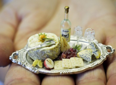 A platter of cheese and biscuits with fruit, wine, silver cheese scoop and wine glasses, made with real glass at he Karon Cunningham Miniatures shop in Bath, UK 16/11/11