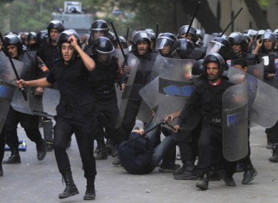 Egyptian police strike a protester during clashes in Tahrir Square today.