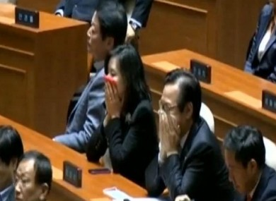 Politicians cover their mouths after tear gas is let off in the South Korean parliament