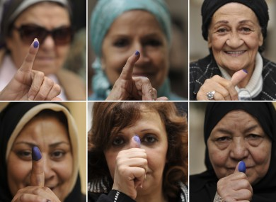 Egyptian women pose with their inked fingers after voting at a polling station in Cairo, Egypt, Tuesday, Nov. 29, 2011