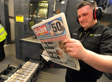 A printer reads one of the first copies of the Sun on Sunday hot off the pre