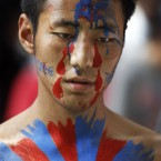 An exile Tibetan, with the Tibetan flag painted on his body, participates in a march in New Delhi, India. (AP Photo/Tsering Topgyal)
