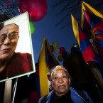 A woman carries a photo of the Dalai Lama opposite the Chinese Embassy during a protest against China's rule in Tibet in Madrid, Spain. (AP Photo/Andres Kudacki)