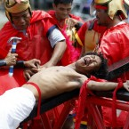 Volunteers dressed as Roman Centurions, drive nails through the palms of an unidentified Catholic devotee in a reenactment of the crucifixion at San Pedro Cutud, Philippines (AP Photo/Bullit Marquez)