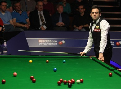 Ronnie O'Sullivan watches the cue miss a red during a snooker in his match with Australia's Neil Robertson earlier today.
