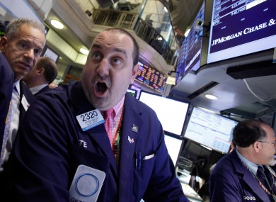 Specialist Peter Giacchi, centre, calls out prices as he works at the post that handles JP Morgan on the floor of the New York Stock Exchange on Friday after the losses were announced.