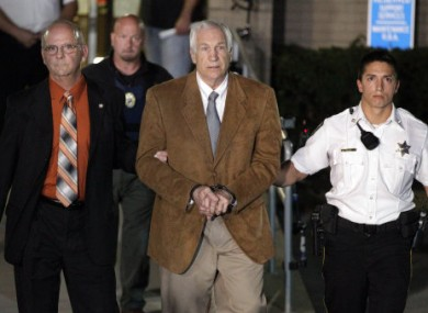 Jerry Sandusky, centre, being led from the court to a police car following his conviction last night.