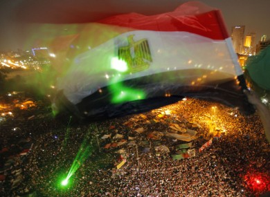An Egyptian waves a national flag over Tahrir Square as people celebrate the election of Mohammed Morsi.