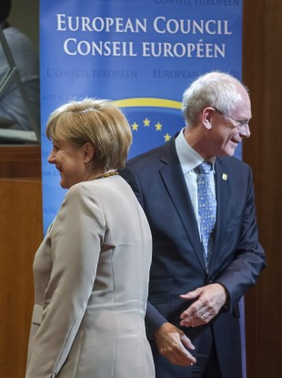 German Chancellor Angela Merkel, left, walks by European Council President Herman Van Rompuy during a round table at the EU Summit in Brussels
