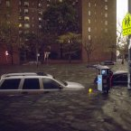 Vehicles are submerged on 14th Street near the Consolidated Edison power plant on Monday in New York. Sandy continued on its path yesterday, as the storm forced the shutdown of mass transit, schools and financial markets, sending coastal residents fleeing, and threatening a dangerous mix of high winds and soaking rain. (AP Photo/ John Minchillo)
