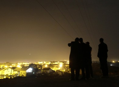 Israelis stand on a hill at the Israeli town of Sderot, background, in southern Israel, overlooking the Gaza Strip last night.