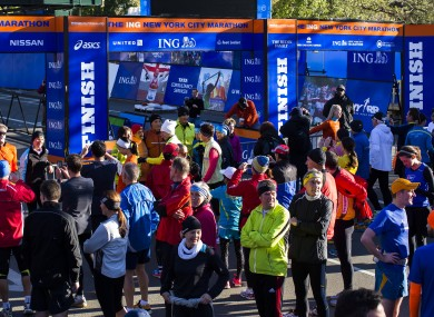 A crowd of runners stands near the barricaded Central Park finish line for the now-canceled New York Marathon.