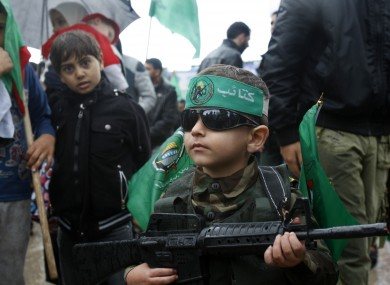 A Palestinian boy wears a green headband with an Arabic slogan and green Islamic flags while holding a toy gun.