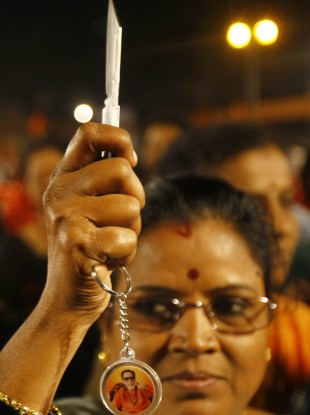 A woman poses for photographs with a knife she received during a distribution by local leaders of Shiv Sena, a right-wing party in Mumbai, India.