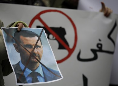 A Syrian immigrant holds a crossed out depiction of Syrian President Bashar al-Assad during a rally against his regime in late 2011.