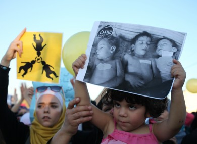 Syrian protesters carry a placards showing dead Syrian children, during a protest in front of the Syrian embassy in Jordan.