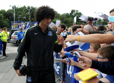 Everton's Marouane Fellaini signs autographs for fans in the Players' Parade outside Goodison Park.