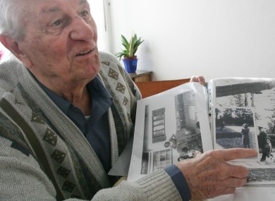 Rochus Misch, pictured in 2005, points to a picture of Adolf Hitler from the early 1940s.